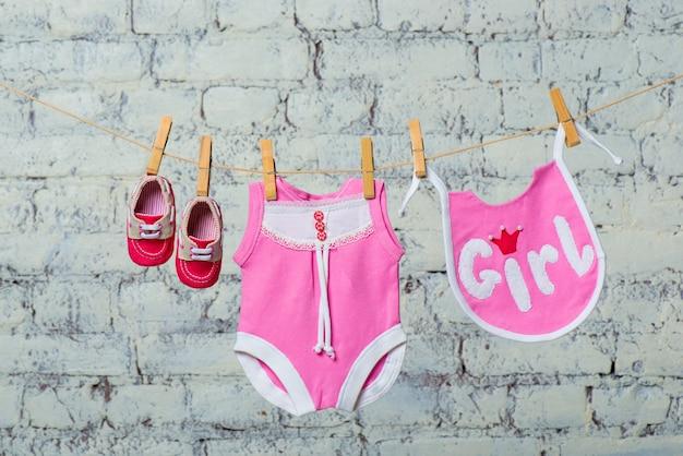 Il pettorale rosa per bambini e le scarpe rosse si asciugano su una corda contro un muro di mattoni bianchi brick