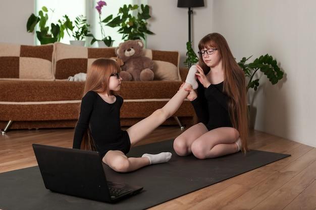 Bambini, sorelle, tenete una sessione di allenamento a casa sul tappetino da ginnastica. ragazze in body da palestra guardano una lezione online su un laptop e fanno stretching.