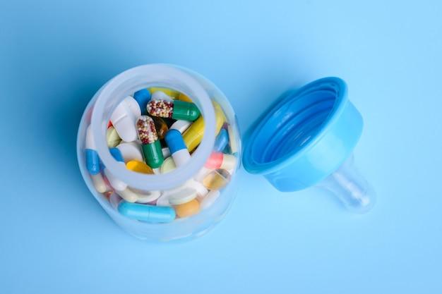 Biberon per bambini per il latte pieno di farmaci in pillole