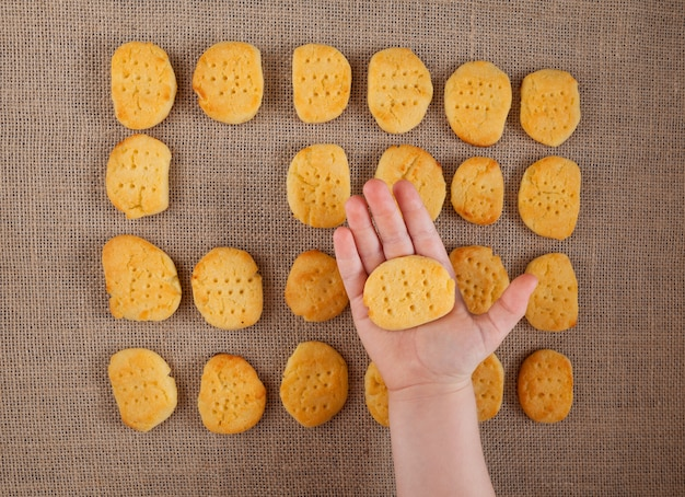 La mano di un bambino tiene un biscotto senza glutine i biscotti fatti in casa si trovano sulla tela da imballaggio