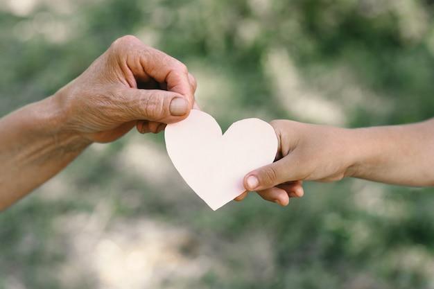 La mano del bambino e la nonna della mano anziana tengono il cuore. idea di concetto di amore famiglia che protegge i bambini e gli anziani nonna amicizia insieme