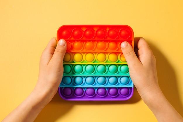 Le mani di un bambino premono sul silicone giocattolo pop it su giallo