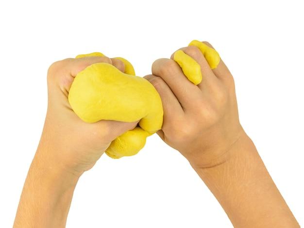 Le mani del bambino stringono la calce gialla isolata su un bianco