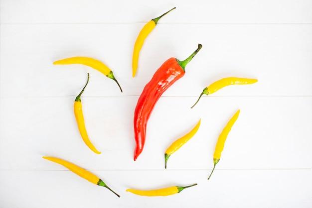 Chili peppers di colore rosso e giallo su fondo di legno bianco.