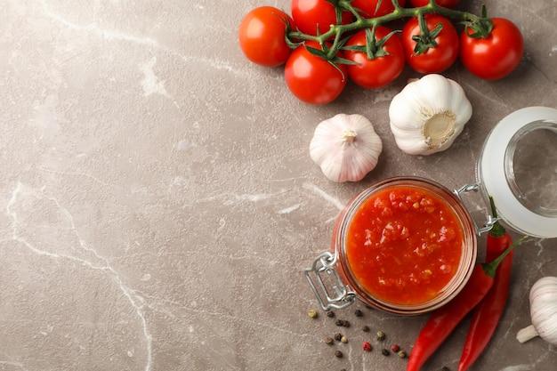 Salsa di peperoncino rosso in barattolo di vetro ed ingredienti su fondo grigio, spazio per testo