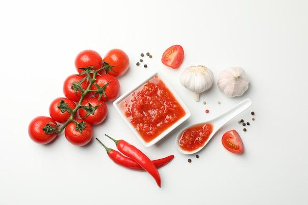 Salsa di peperoncino rosso in barattolo di vetro ed ingredienti su fondo bianco, spazio per testo. vista dall'alto
