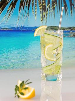Cocktail freddo con limone e ghiaccio sullo sfondo della spiaggia, del mare blu e del cielo blu blue