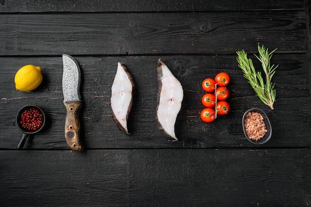 Set di bistecche di halibut refrigerate, con ingredienti ed erbe di rosmarino, su sfondo di tavolo in legno nero, vista dall'alto piatta, con spazio di copia per il testo