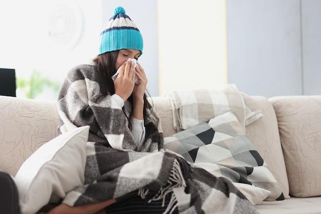Donna raffreddata sul divano in coperta e cappello tiene il fazzoletto
