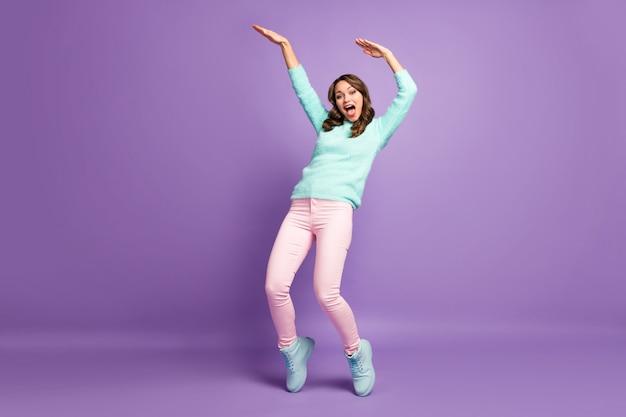 Agghiacciante signora divertente alza le mani ballando giovani mosse moderne pazzo abbigliamento da studente casual pullover soffice pantaloni rosa pastello scarpe.