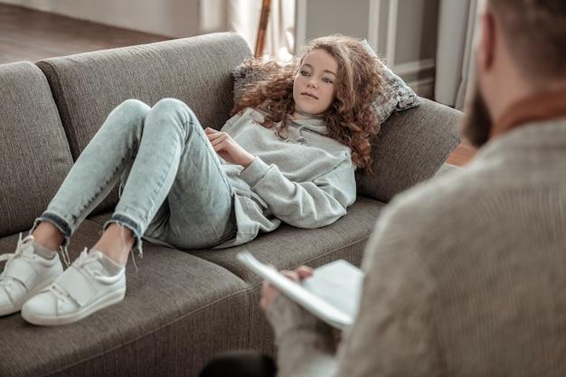 Rilassarsi sul divano. adolescente riccia che indossa una felpa con cappuccio grigia che si rilassa sul divano e parla con il consigliere