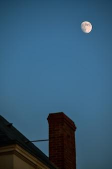 Camino e tetto sfocati, con la luna