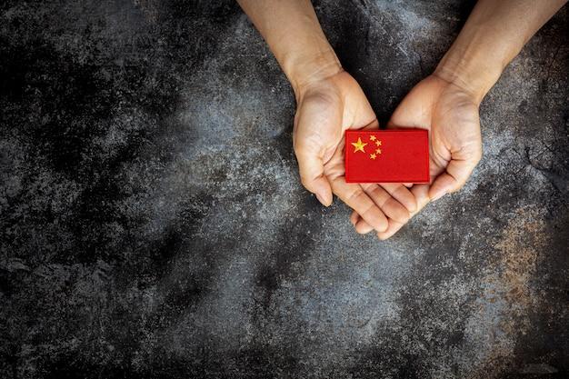 Bandiera della cina sulle mani. concetto di amore, cura, protezione e sicurezza.