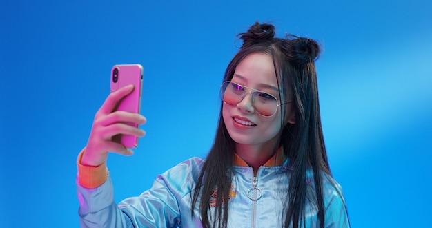 Ragazza di chines che prende selfie allo studio con effetti al neon.