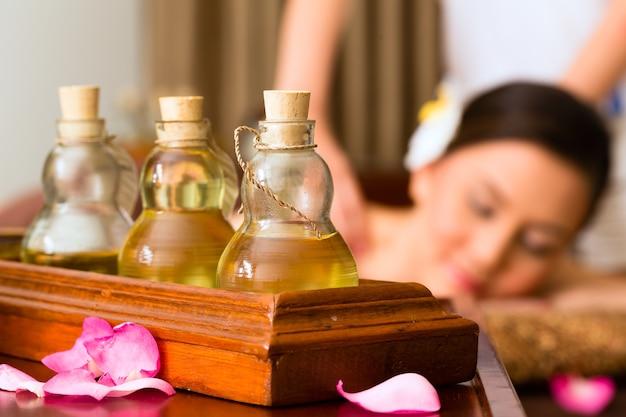 Donna asiatica cinese nel centro termale di bellezza benessere con massaggio aromaterapico con olio essenziale, guardando rilassato