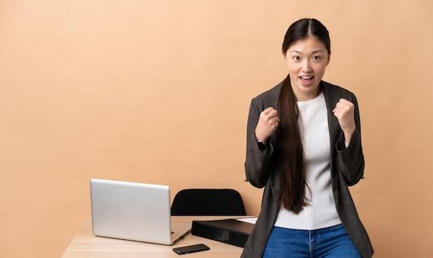 Donna d'affari cinese nel suo posto di lavoro che celebra una vittoria nella posizione del vincitore