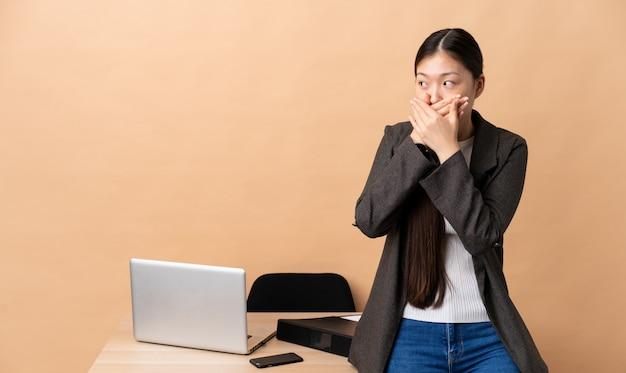 Donna d'affari cinese nel suo posto di lavoro che copre la bocca e guardando al lato