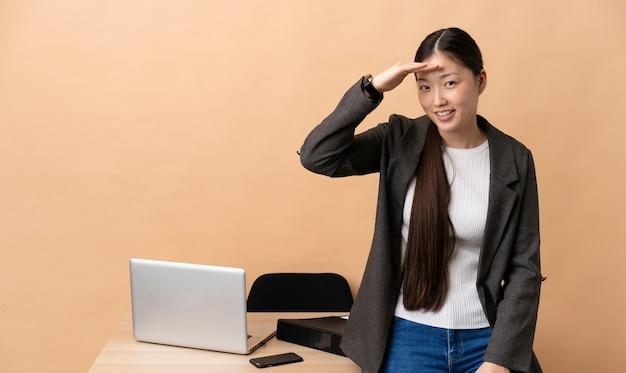 Donna d'affari cinese nel suo posto di lavoro che guarda lontano con la mano per guardare qualcosa