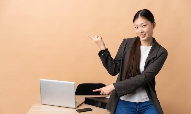 Donna d'affari cinese nel suo posto di lavoro che punta il dito