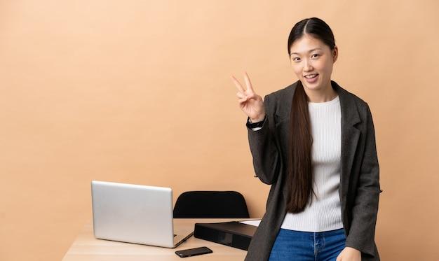 Donna cinese di affari nel suo posto di lavoro che sorride e che mostra il segno di vittoria