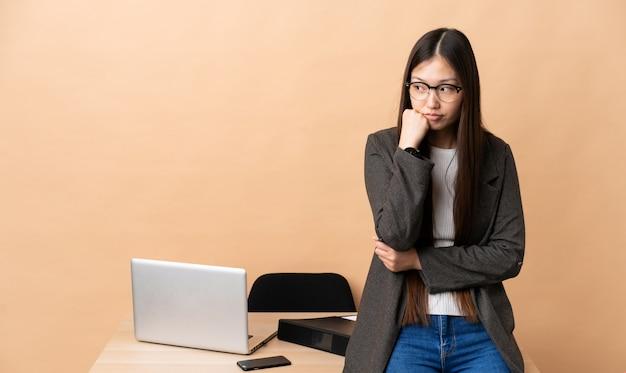 Donna cinese di affari nel suo posto di lavoro con l'espressione stanca e annoiata