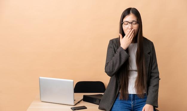 Donna cinese di affari nel suo posto di lavoro che sbadiglia e che copre la bocca spalancata con la mano
