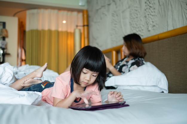 Telefono dipendente da bambino cinese, ragazza asiatica che gioca smartphone, fumetto che guarda il bambino