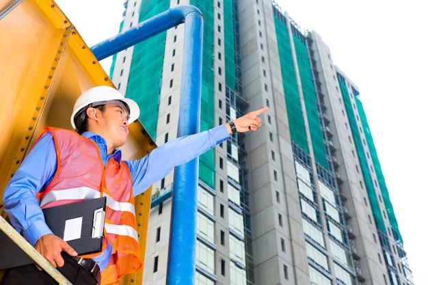 Operaio edile cinese o supervisore o architetto con appunti in un cantiere edile in asia