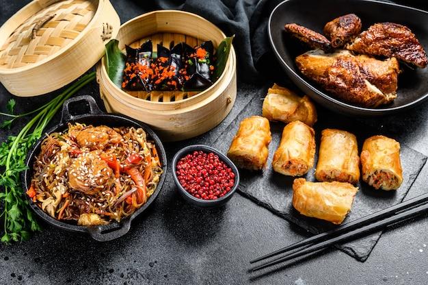 Set di piatti di cucina cinese, sfondo nero di cibo. tagliatelle cinesi, gnocchi, anatra alla pechinese, dim sum, involtini primavera. famoso. vista dall'alto