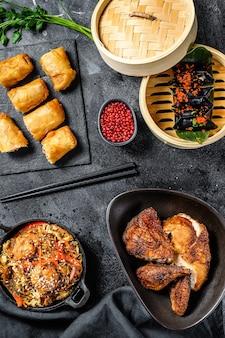 Set di piatti di cucina cinese, cibo sfondo nero. spaghetti cinesi, gnocchi, anatra alla pechinese, dim sum, involtini primavera