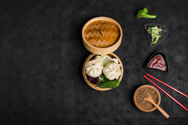 Gnocco cinese in una scatola di bambù a vapore con insalata; ciotola di semi di coriandolo e salsa su sfondo nero