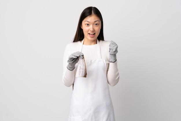 Peschereccio cinese che indossa un grembiule e tiene un pesce crudo su sfondo bianco isolato che celebra una vittoria nella posizione del vincitore