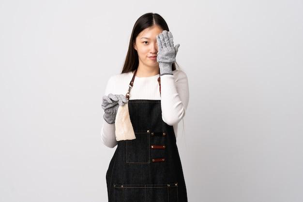 Il pescivendolo cinese indossa un grembiule e tiene un pesce crudo su uno sfondo bianco isolato che copre gli occhi con le mani