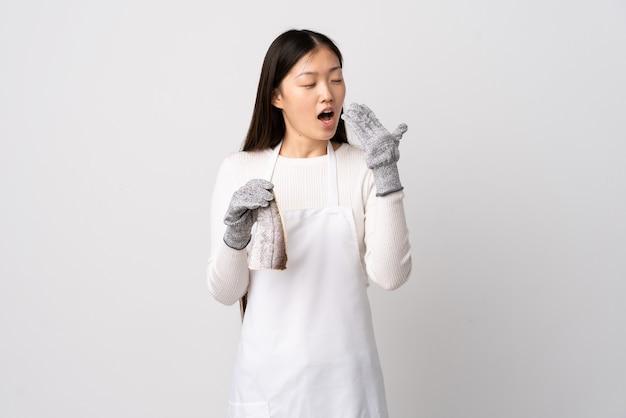 Pescivendolo cinese che indossa un grembiule e tenendo un pesce crudo su sfondo bianco isolato che sbadiglia e che copre la bocca spalancata con la mano