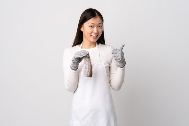 Pescivendolo cinese che indossa un grembiule e che tiene un pesce crudo sopra bianco isolato che dà un pollice in alto gesto