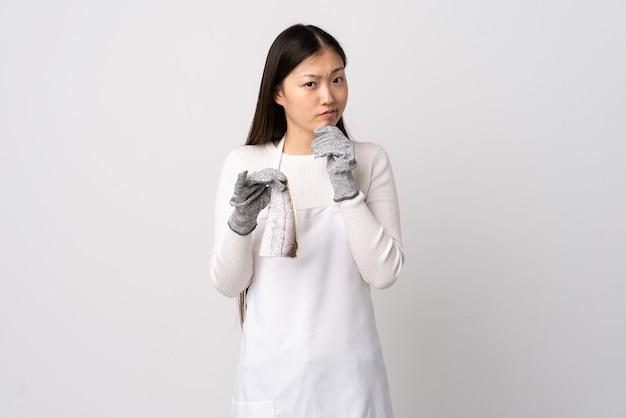 Pescivendolo cinese che indossa un grembiule e che tiene un pesce crudo sopra bianco isolato che ha dubbi e che pensa