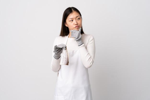 Pescivendolo cinese che indossa un grembiule e che tiene un pesce crudo su bianco isolato che ha dubbi
