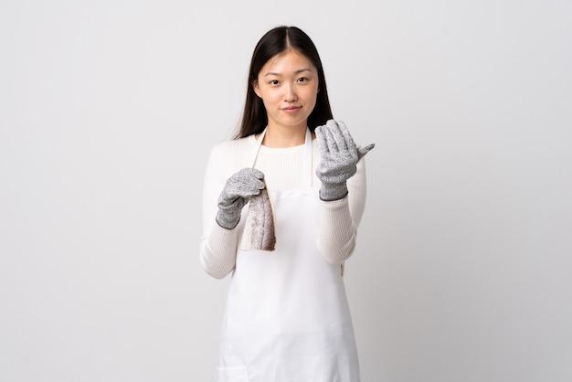 Pescivendolo cinese che indossa un grembiule e che tiene un pesce crudo sopra bianco isolato che invita a venire con la mano