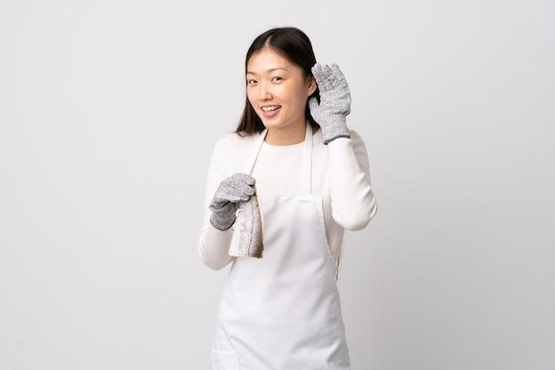 Pescivendolo cinese che indossa un grembiule e che tiene un pesce crudo sopra bianco isolato che ascolta qualcosa mettendo la mano sull'orecchio