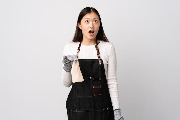 Pescivendolo cinese che indossa un grembiule e che tiene un pesce crudo sopra bianco isolato che osserva in su e con l'espressione sorpresa