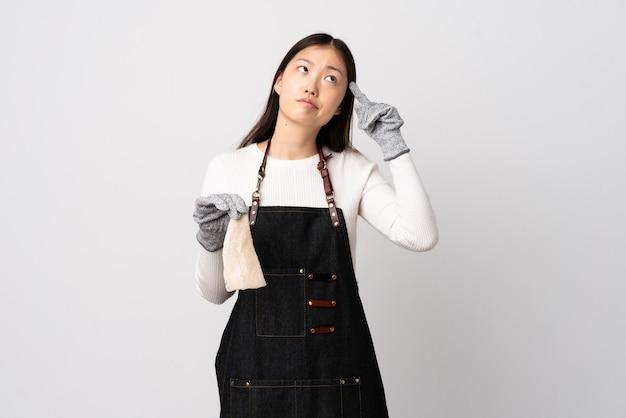 Pescivendolo cinese che indossa un grembiule e che tiene un pesce crudo su bianco isolato facendo il gesto della follia mettendo il dito sulla testa