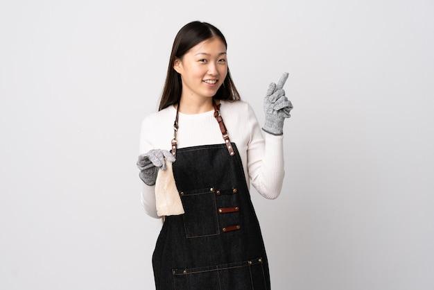 Pescivendolo cinese che indossa un grembiule e che tiene un pesce crudo sopra il bianco isolato che indica con il dito indice una grande idea