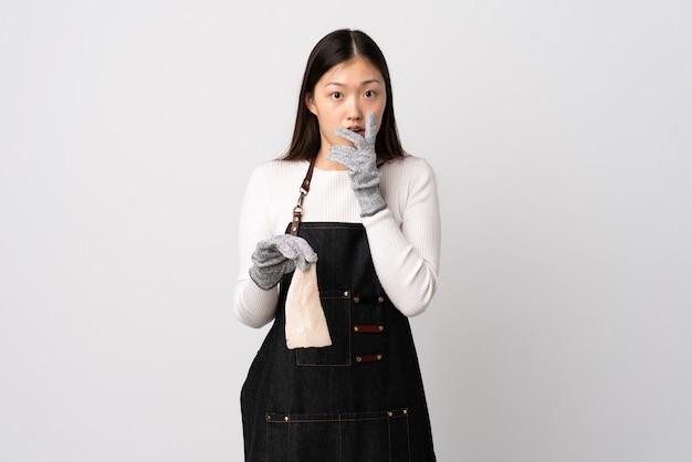 Pescivendolo cinese che indossa un grembiule e che tiene un pesce crudo sopra bianco isolato sorpreso e scioccato mentre guarda a destra