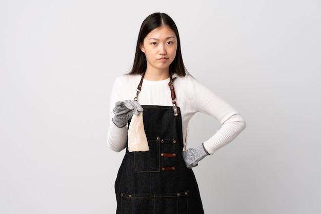 Pescivendolo cinese che indossa un grembiule e che tiene un pesce crudo sopra il muro bianco isolato arrabbiato