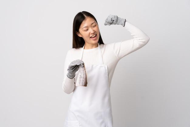 Pescivendolo cinese che indossa un grembiule e che tiene un pesce crudo sopra la parete bianca isolata che celebra una vittoria