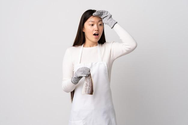 Pescivendolo cinese che indossa un grembiule e che tiene un pesce crudo sopra la parete bianca isolata che fa il gesto di sorpresa mentre guarda al lato