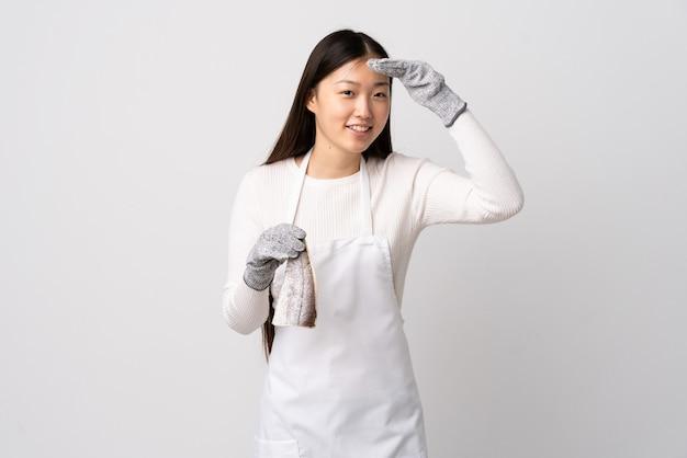 Pescivendolo cinese che indossa un grembiule e che tiene un pesce crudo sopra il muro bianco isolato che guarda lontano con la mano per guardare qualcosa