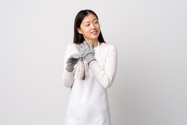 Pescivendolo cinese che indossa un grembiule e che tiene un pesce crudo sopra la parete bianca isolata che osserva in su mentre sorride