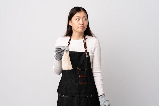 Pescivendolo cinese che indossa un grembiule e che tiene un pesce crudo sopra la parete bianca isolata che fa gesto di dubbio che osserva lato