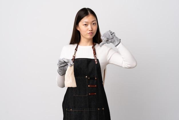 Pescivendolo cinese che indossa un grembiule e che tiene un pesce crudo sopra il muro bianco isolato orgoglioso e soddisfatto di sé